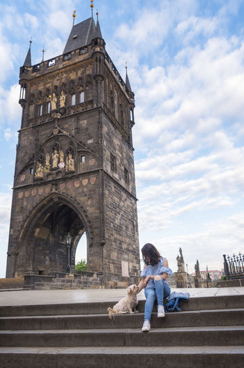 Woman sitting with dog on steps against historical building