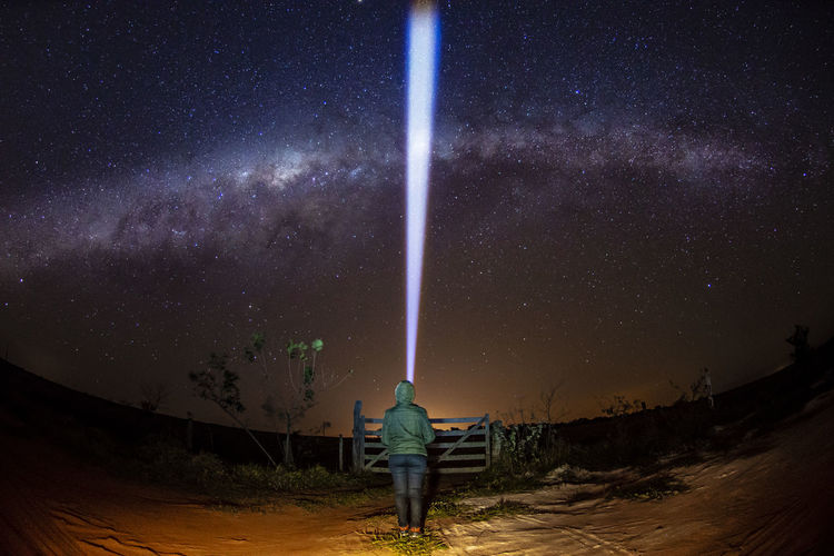 Rear view of woman with illuminated flashlight standing against star field at night