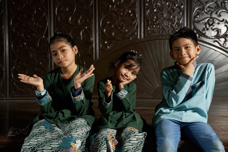 Malay kids with traditional clothing sitting together with hand gesture love