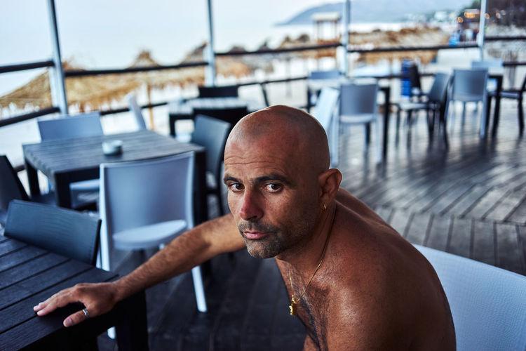 Portrait of shirtless man sitting at resort