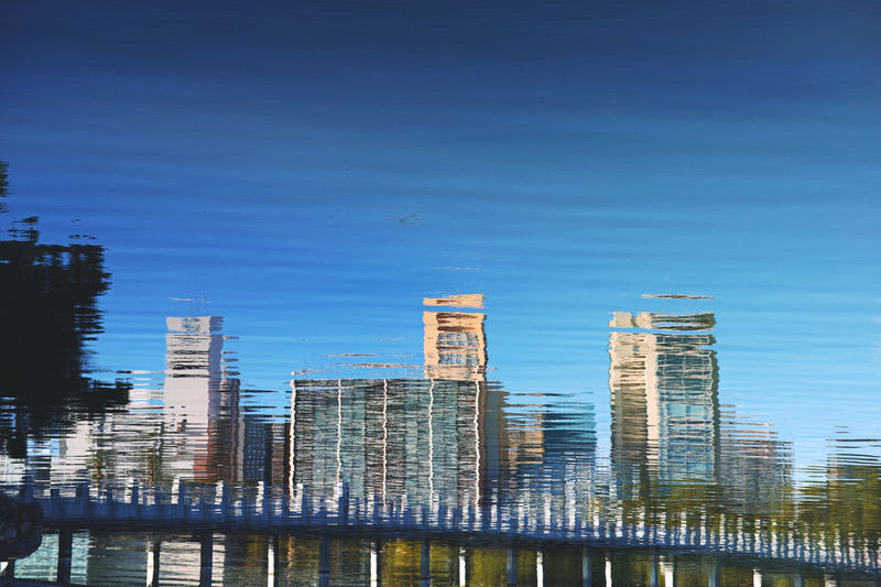 Buildings reflecting on river in city