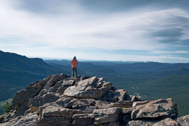 Rear View Of Man Standing On Rock At Mountain Against Sky