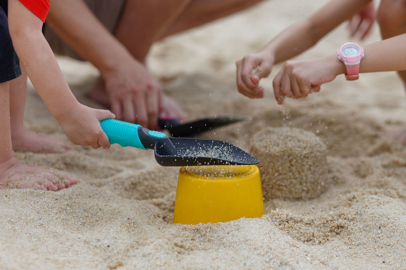 Cropped image of siblings making sand castle at beach