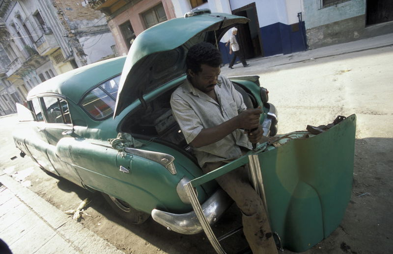 Tilt Image Of Man Repairing Car On Street