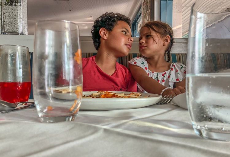 Low angle view of teenager boy and girl sitting at table