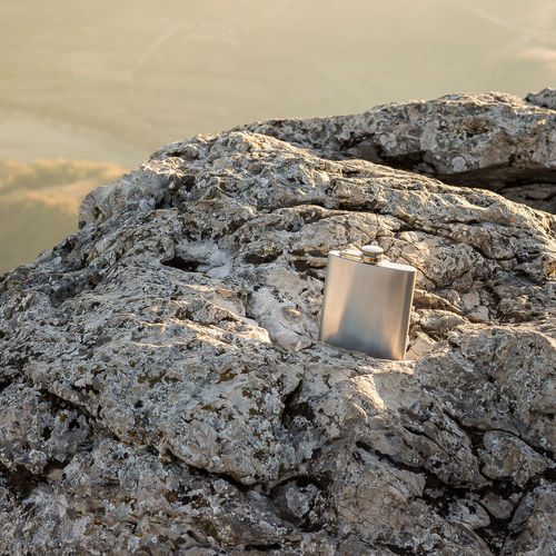 Beautifully sunlit metallic alcohol flask on a contrasty rock Light Bottle Drink Container Sunlight Alcohol Square Addiction Texture Cap Silver  Whiskey Closed Rock Formation Rough Chrome Aluminum Close-up Stainless Steel  Metallic Flask No People Sunlit Hip Flask EyeEmNewHere