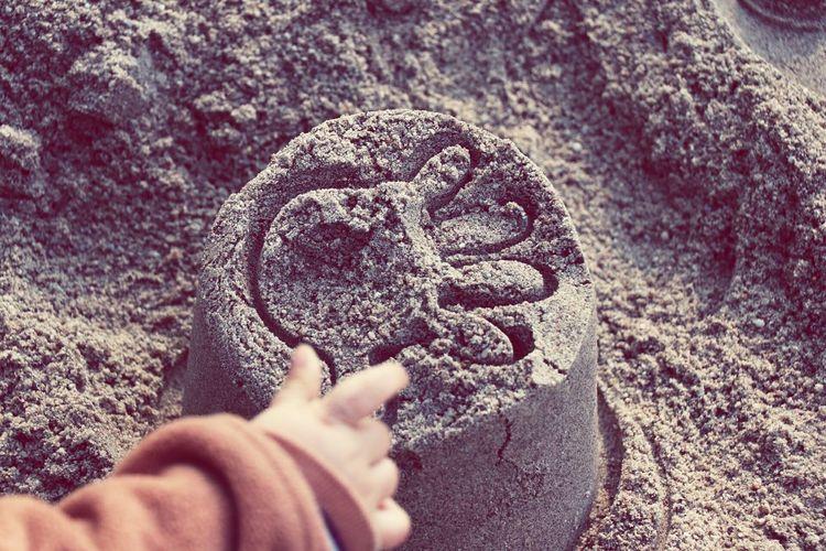 Child's hand on sand