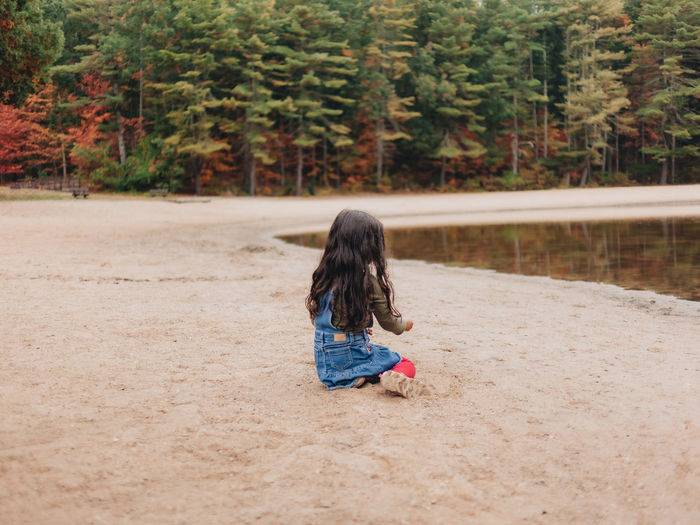 Girl playing by lake on a lovely autumn or fall day