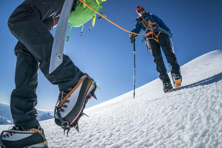 People skiing on snow against mountain range