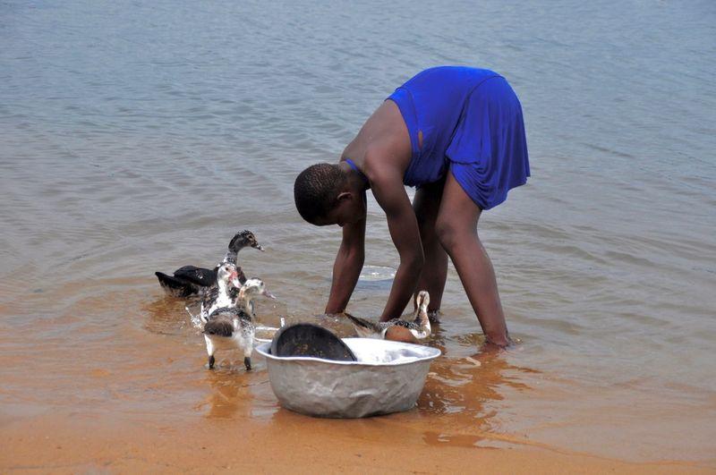 Woman washing kitchen utensil in lake