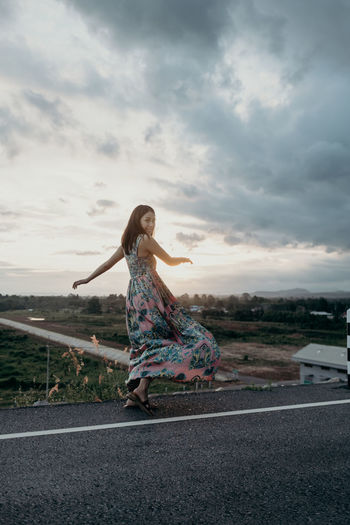 Woman with umbrella on road against sky at sunset