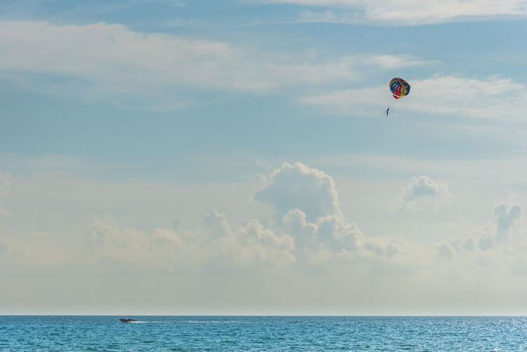 Distant view of person parasailing over sea against cloudy sky