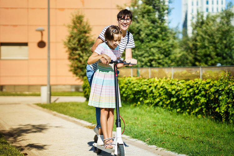 Mother with daughter riding push scooter on footpath