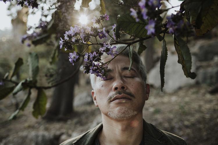 Portrait of man against purple flowering plants