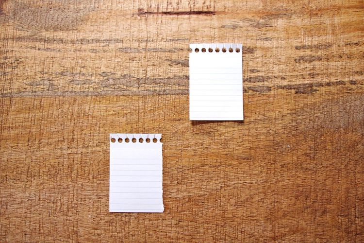 Close-up of empty papers on wooden table