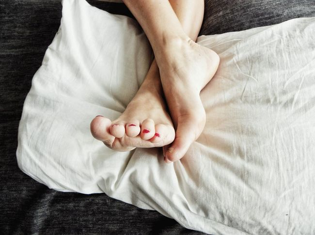 Human Body Part Barefoot One Woman Only Human Foot Toe Bed Indoors  Human Leg Nail Polish Women One Young Woman Only Contrasting Colors Pillow Sleeping Taking A Rest  Legs On Pillow Lifestyles Woman Legs Bed Relaxation Light Comfort Resting Pedicure Comfortable