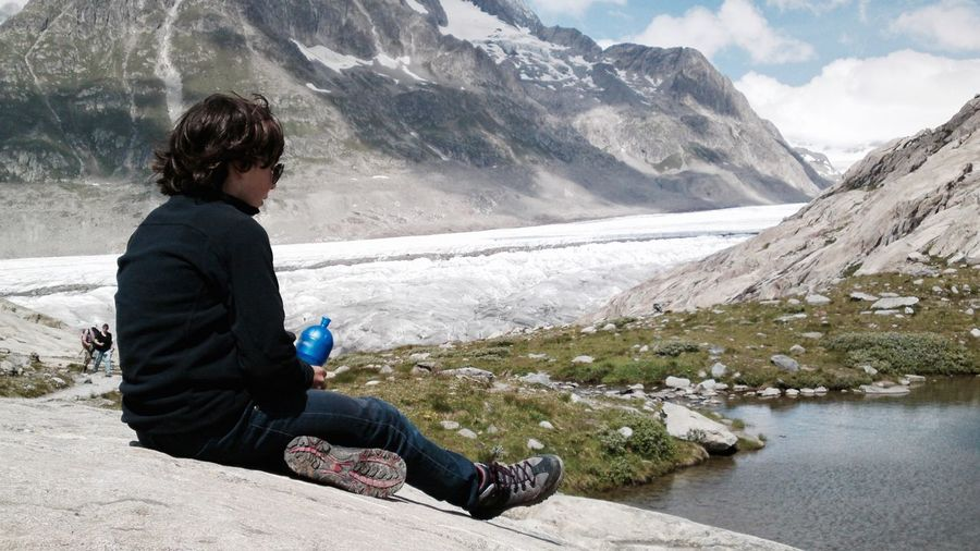 Pre-Adolescent Boy Sitting On Mountain At Aletsch Glacier