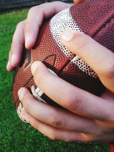 Cropped Image Of Hands Holding Rugby Ball On Grassy Field