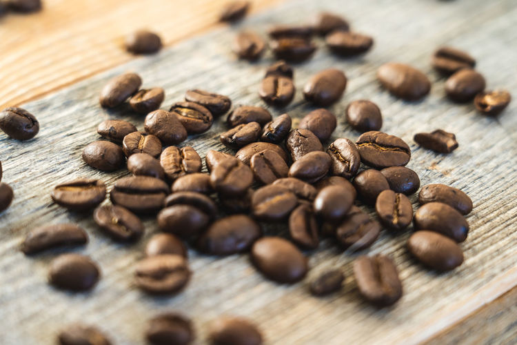 Close-up shot of roasted coffee beans on rustic wooden boards Wood - Material Food And Drink Table Food Selective Focus Brown Freshness Still Life Roasted Coffee Bean Large Group Of Objects Close-up Coffee Coffee - Drink No People Indoors  Abundance Roasted Wellbeing High Angle View Drink Caffeine