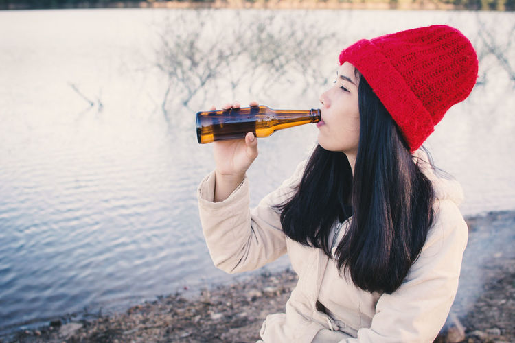 Young woman drinking beer at lakeshore