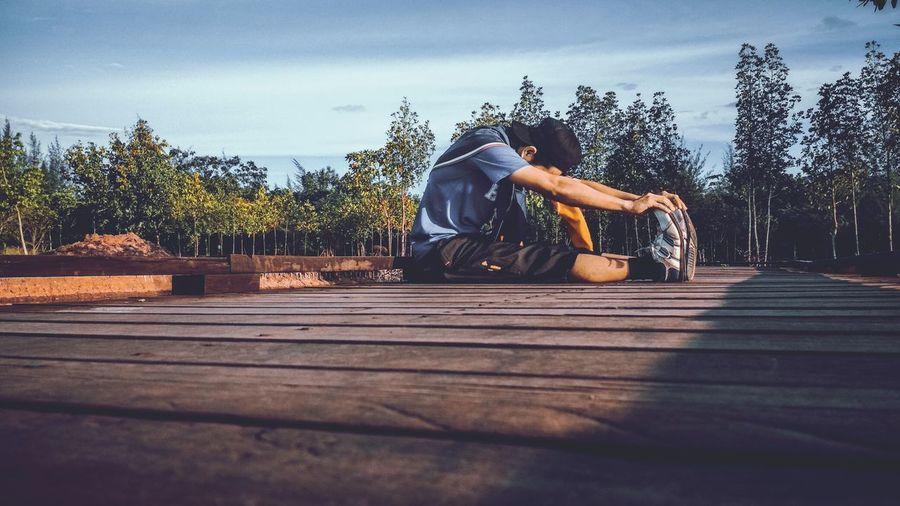 Man sitting on wooden log against sky