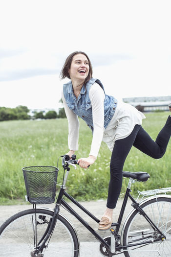 Portrait of smiling young woman riding bicycle