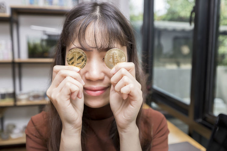 Close-up of woman holding bitcoin at home