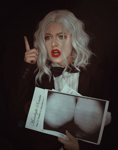 Angry Young Woman Holding Photograph Against Black Background