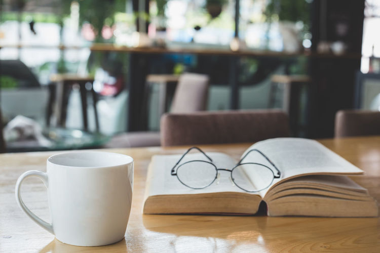 Coffee with book Business Cafe Coffee Coffee - Drink Coffee Cup Crockery Cup Drink Eyeglasses  Focus On Foreground Food And Drink Glasses Indoors  Mug No People Publication Refreshment Restaurant Still Life Table Tea Cup Wood - Material