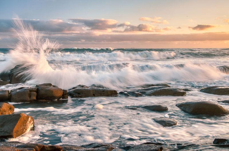 Waves splashing on rocks against sky during sunset