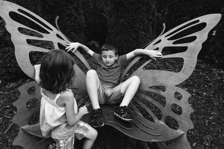 Siblings playing with wing shaped chair