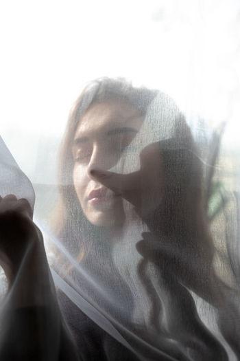 Portrait of woman in glass window