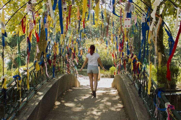 Rear View Full Length Of Woman Amidst Colorful Ribbon Decorations On Footbridge