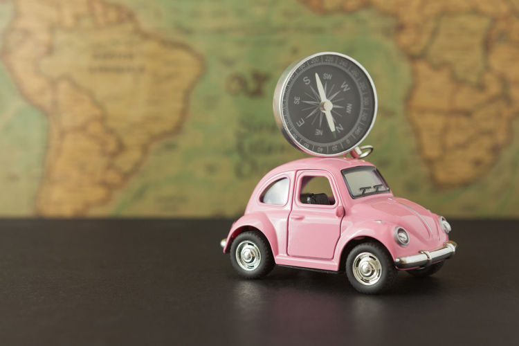 Close-up of toy car and navigational compass on table