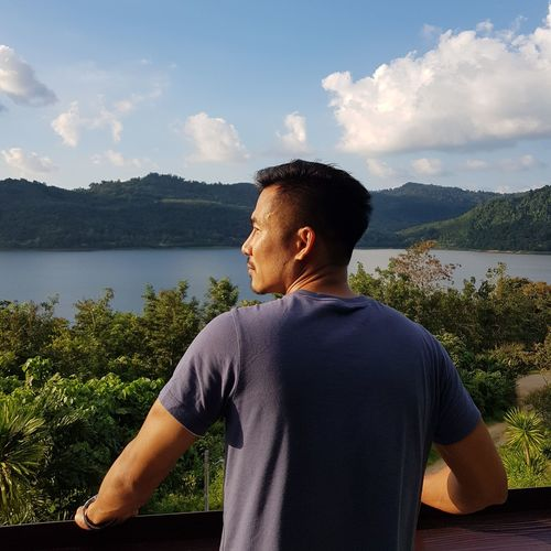 Young man looking at lake against sky