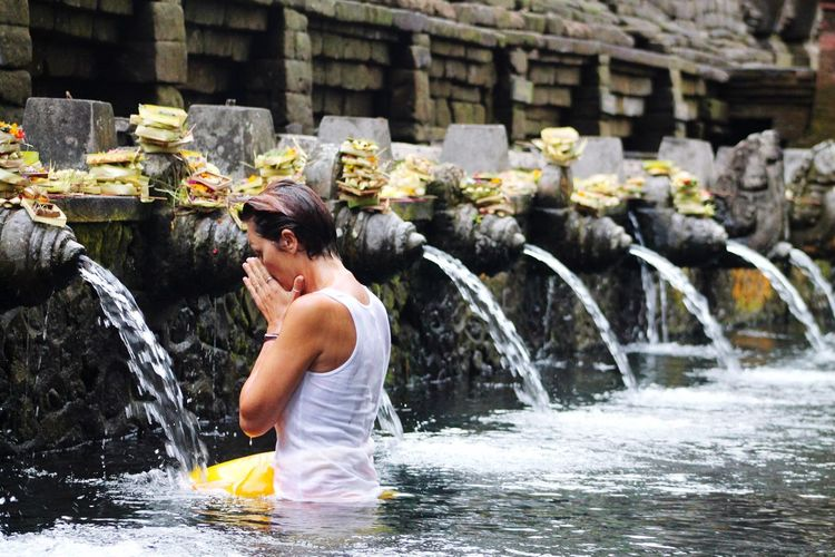 Side View Of Woman Bathing At Tirta Empul Temple