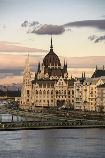 Hungarian parliament building and river against sky