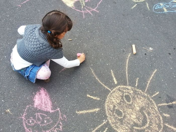 High angle view of a girl drawing on street