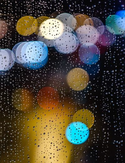 Close-up of water drops on multi colored glass