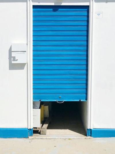 Closed and open blue door of building