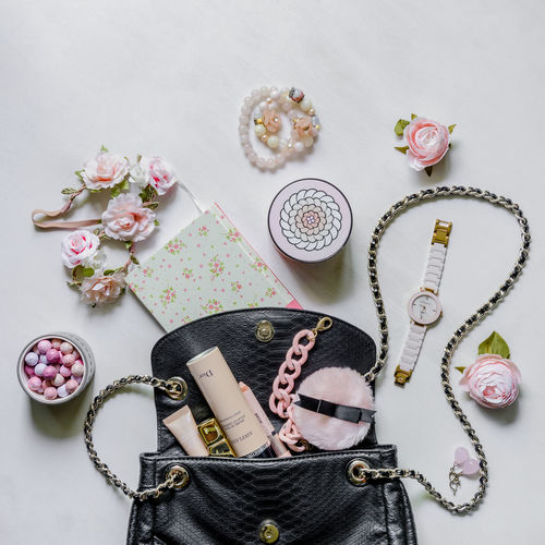 What's inside a woman's handbag Art And Craft Choice Close-up Creativity Decoration Design Directly Above Flatlay Flower High Angle View Indoors  Large Group Of Objects No People Pattern Still Life Studio Shot Table Variation White Background
