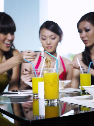 Female friends eating spaghetti while sitting in restaurant