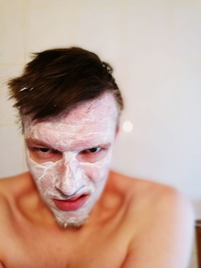 Portrait of shirtless man making face while wearing mask at home