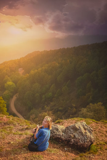 Portrait of woman sitting by cliff against sky