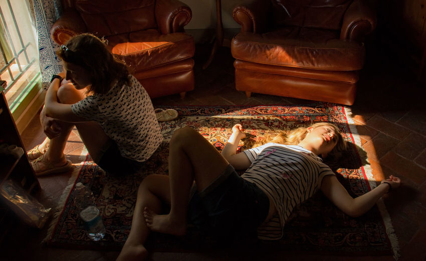 High Angle View Of Woman Lying By Friend On Carpet At Home