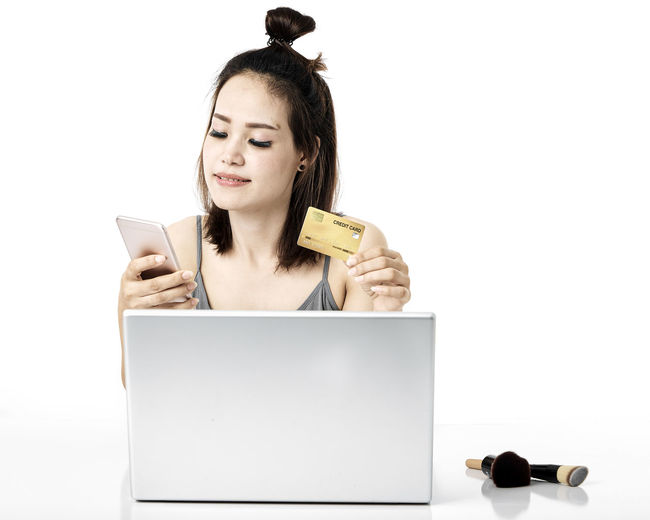 Asian woman shopping online studio shot on white background, for online shopping, technology and internet concept, Thai Studio Shot 30-34 Years Shopping Online  Young Female Happy Asian  Laptop Beautiful Internet Attractive Smile person Computer People Portrait Holding Phone Beauty Mobile Pretty Technology Payment Adult Using Lifestyle Cheerful Purchase Business Wireless Lady Chinese Fashion Looking Smartphone Japanese  Korean Credit Card Empty Text Copy Space White Background One Person Wireless Technology Cut Out Indoors  Communication Young Adult Front View Women Young Women Connection Finance Lifestyles Hair Hairstyle Using Laptop Beautiful Woman