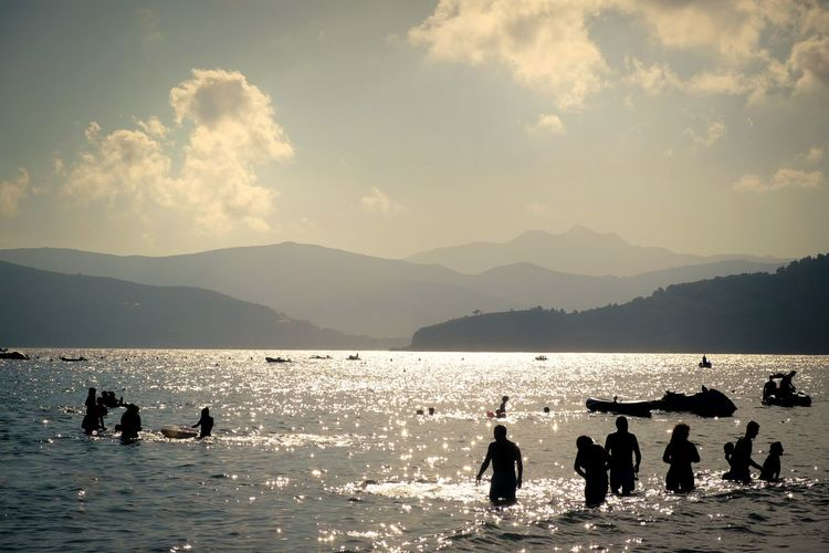 Silhouette people on sea by mountains against sky