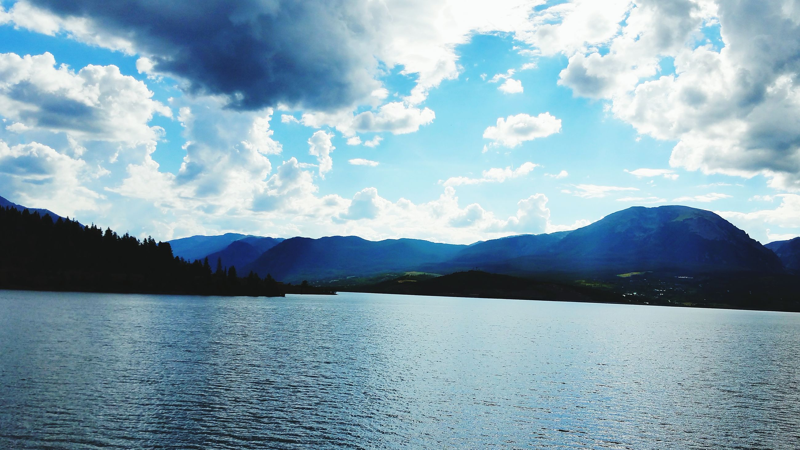 mountain, water, tranquil scene, sky, scenics, mountain range, tranquility, beauty in nature, waterfront, cloud - sky, nature, sea, cloud, lake, idyllic, cloudy, rippled, river, non-urban scene, outdoors
