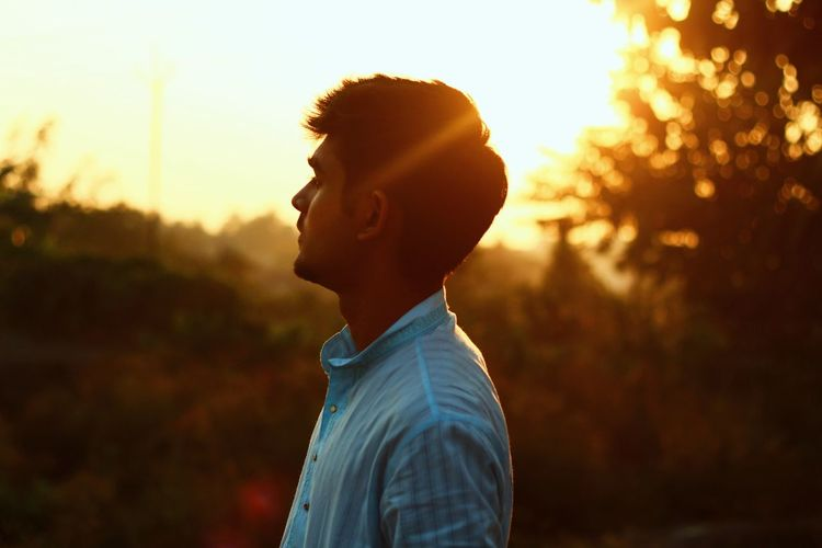 Young man standing against sky during sunset