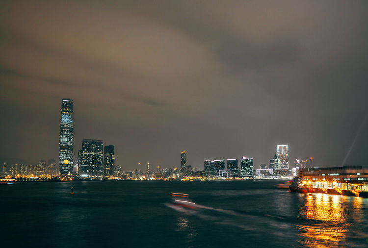 Scenic View Of Sea By Illuminated Cityscape Against Sky At Night